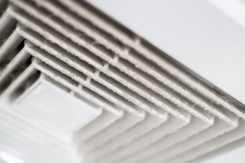 Air duct grille covered by layer of dust and debris