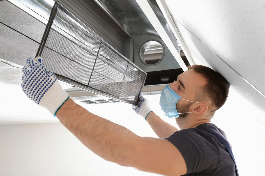 Professional air duct cleaning technician removing dirty air duct filter